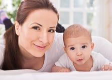Mère de détente avec le bébé à la maison Photos stock