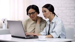 Mère de enseignement de fille pour utiliser l'ordinateur portable, montrant le logiciel utile, culture informatique photo stock