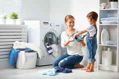 Mère de famille et fille d'enfant dans le machi de lavage proche de buanderie photos stock