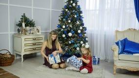 Mère de famille et fille heureuses d'enfant le matin de Noël à l'arbre de Noël avec des cadeaux Photographie stock libre de droits