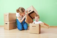 Mère de famille et fille heureuses de bébé dans un appartement vide avec Photo stock