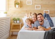 Mère de famille, père et rires heureux d'enfant dans le lit Photographie stock libre de droits