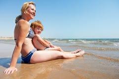 Femme et petit enfant à la plage de mer Image stock