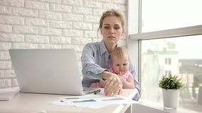 Mère de fonctionnement avec le bébé à la table Mère active avec le beau nourrisson sur des mains clips vidéos