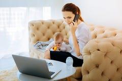 Mère de fonctionnement occupée parlant au téléphone Photos libres de droits