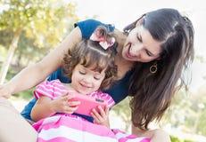 Mère de métis et service de mini-messages mignon de fille de bébé au téléphone intelligent Image libre de droits