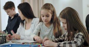 Mère de plan rapproché avec ses enfants passant le temps ensemble ils dessinant et jouant un jeu de table dans le salon, très clips vidéos