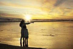 Mère de silhouette et sa fille au rivage Image stock
