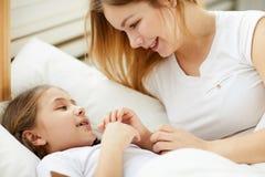 Mère de soin étendant la fille pour dormir photos libres de droits