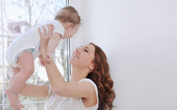 Mère de soin heureuse jouant avec son bébé garçon mignon Photographie stock