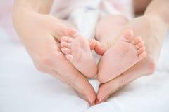 Mère de soins tenant garder des jambes de son nourrisson Image libre de droits