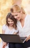 Mère de sourire et petite fille avec l'ordinateur portable Image stock