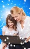 Mère de sourire et petite fille avec l'ordinateur portable Images libres de droits