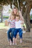 Mère de sourire et sa oscillation d'enfants photos stock