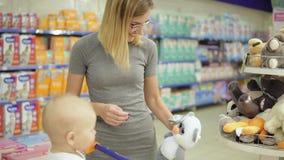 Mère de sourire et son enfant dans le département de jouet dans le supermarché choisissant des jouets Petit bébé mignon s'asseyan banque de vidéos