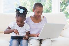 Mère de sourire heureuse à l'aide de l'ordinateur portable avec sa fille à l'aide du comprimé sur le divan Images stock