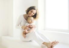Mère de sourire heureuse avec la maison de bébé dans la chambre blanche près de la fenêtre Photos stock