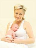 Mère de sourire heureuse avec la maison de bébé de sommeil Photos stock