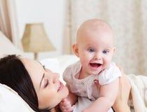 Mère de sourire heureuse avec le vieux bébé de six mois Photo stock