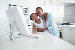 Mère de sourire heureuse avec sa fille à l'aide de l'ordinateur Image stock