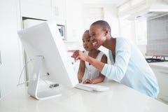 Mère de sourire heureuse avec sa fille à l'aide de l'ordinateur photos libres de droits