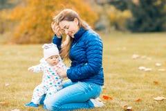 Mère de sourire heureuse jouant avec l'enfant dans le jour chaud d'automne images libres de droits