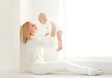 Mère de sourire heureuse jouant avec la maison de bébé dans le nea de chambre blanche Photographie stock