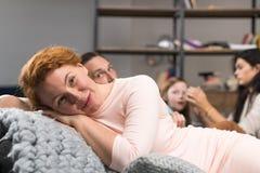 Mère de sourire heureuse se trouvant sur le divan au-dessus du fond de communication de famille, parents passant le temps avec de Images stock