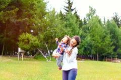 Mère de sourire jetant le petit garçon gai d'enfant en bas âge Photos stock