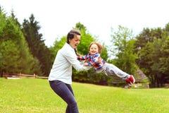 Mère de sourire jouant avec le fils d'enfant en bas âge en parc Images libres de droits