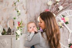 Mère de sourire jouant avec le fils de bébé à la maison Image stock