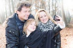 Mère de sourire, père et petite fille faisant le selfie avec l'appareil-photo Image libre de droits