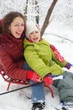 Mère de sourire, pose de descendant sur le traîneau Images stock