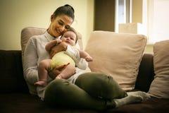 Mère de sourire s'asseyant sur le divan et tenir le bébé dans des bras image stock