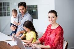 Mère de sourire travaillant sur l'ordinateur portable avec la fille de aide de père dans le travail photos stock