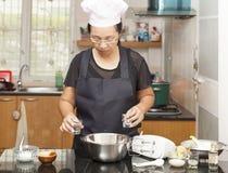 Mère disposant des ingrédients pour faire le gâteau mousseline Photographie stock libre de droits
