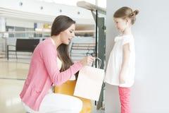 Mère donnant à fille le sac à provisions de papier Photographie stock libre de droits