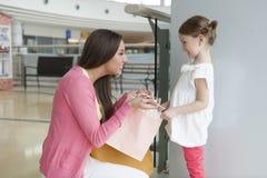 Mère donnant à fille le sac à provisions de papier Photos libres de droits