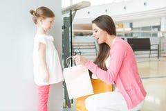 Mère donnant à fille le sac à provisions de papier Photographie stock