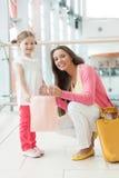 Mère donnant à fille le sac à provisions de papier Image stock