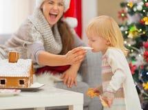 Mère donnant des biscuits de Noël de dégagement à la chéri photo libre de droits
