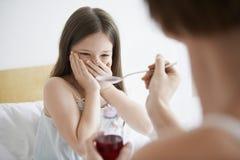 Mère donnant le sirop de toux à la fille de réticence images libres de droits