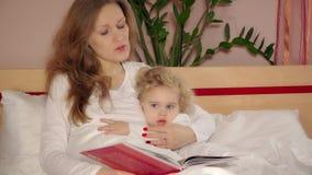 Mère embrassée heureuse et livre de lecture mignon de fille de fille avant sommeil banque de vidéos