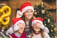 Mère embrassant avec des enfants dans des chapeaux de Santa Photo stock