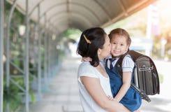 Mère embrassant l'écolière dans l'uniforme photos stock