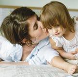 Mère embrassant la fille avec amour Photographie stock