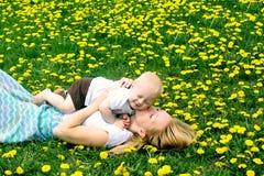 Mère embrassant le bébé en pissenlits Photographie stock