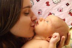 Mère embrassant son enfant Photo stock