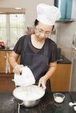 Mère employant le mélangeur électrique pour mélanger des ingrédients de gâteau mousseline Image libre de droits