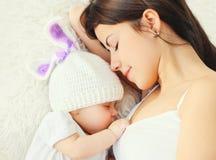 Mère en gros plan de portrait jeune dormant avec le bébé sur le lit à la maison images stock